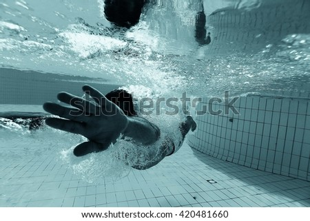 man dives into the pool underwater photo