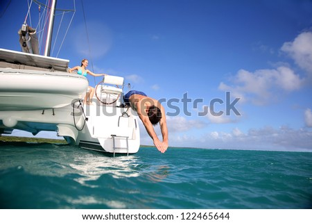 Man diving from catamaran deck into the sea - stock photo