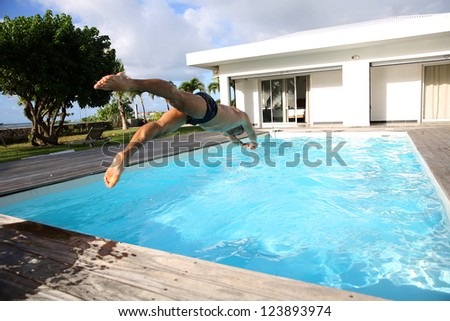 Man diving in private swimming-pool - stock photo