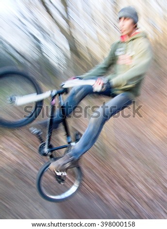 Man does a trick on bicycle motocross bike (trick - tailwhip). He rides in discipline of dirt jumping in the forest. Due to the long exposure he blurred.  - stock photo