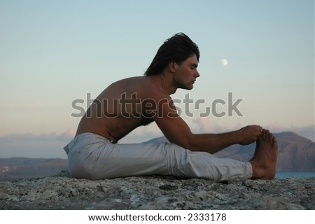 Man doing a paschimottanasana yoga posture (variant)