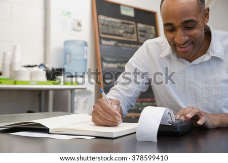 Man doing accounts in cafe