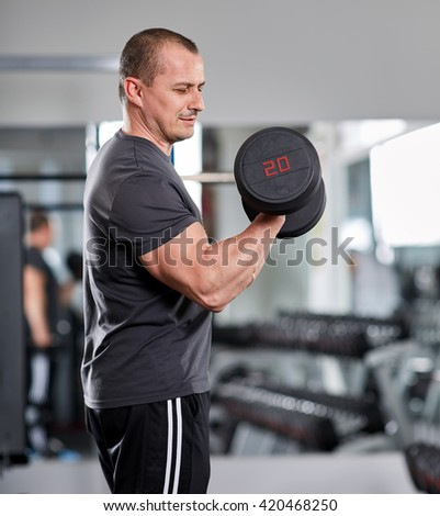 Man doing biceps curl standing in the gym with selective focus - stock photo