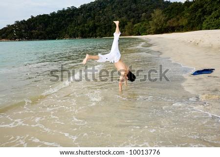 man doing cartwheel by he beach - stock photo