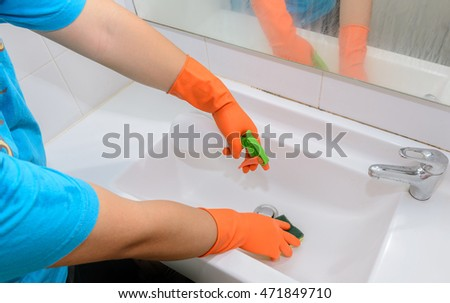 man doing chores in bathroom at home, cleaning sink and faucet with spray detergent. Cropped view