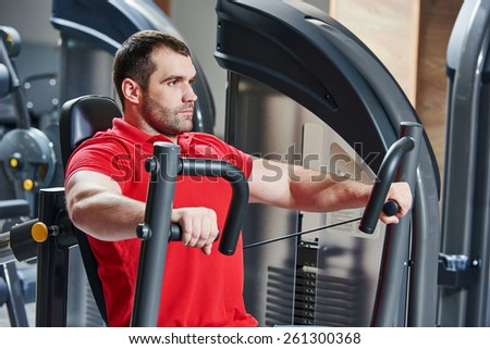 man doing excercises with weight training equipment on sport gym club - stock photo