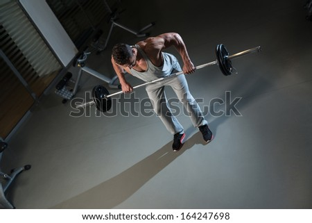 Man Doing Exercise For Back With Barbell. Man Doing Heavy Weight Exercise For Back - stock photo