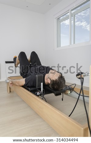 Man doing exercise of pilates with reformer bed.