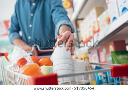Man doing grocery shopping at the supermarket, he is putting a bottle of milk in the cart