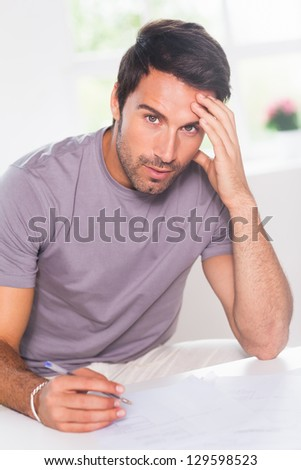 Man doing his accounting and looking at camera in kitchen