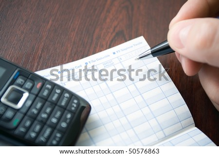 Man doing home finances on transaction register notebook. Shallow depth of field with focus on pen. - stock photo