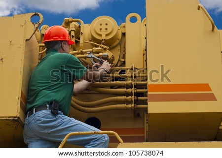 man doing maintenance work on a large piece of machinery - stock photo