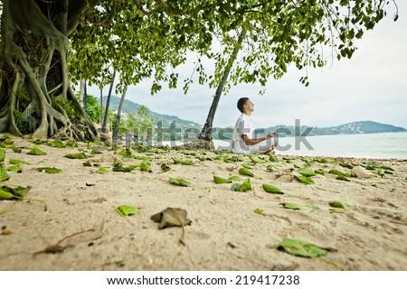 Man doing meditation exercises on the beach  - stock photo