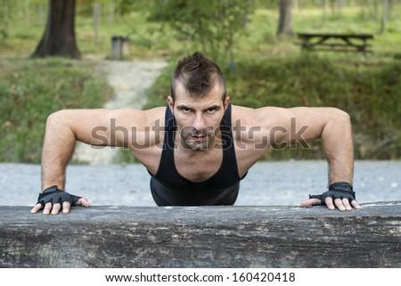 Man doing push up on wooden log. - stock photo