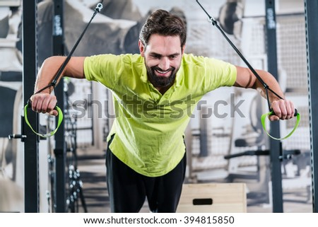 Man doing pushup with rings in functional training gym - stock photo