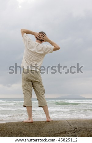 Man doing relaxing exercises on a rock at the sea - stock photo