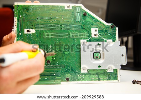 man doing repairs on a circuit board with a soldering iron - stock photo