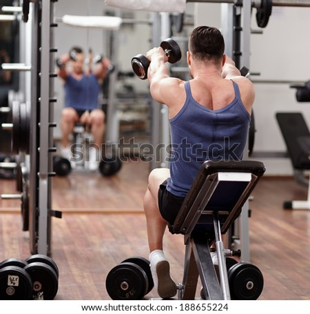 Man doing shoulders and back workout in front of the mirror in the gym