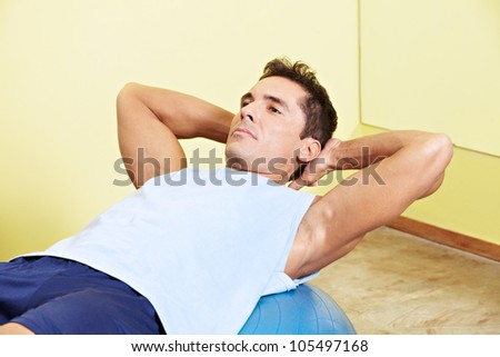Man doing sit-ups in fitness center on gym ball - stock photo
