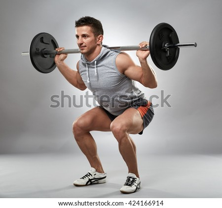 Man doing squats with barbell on neck back, studio shot
