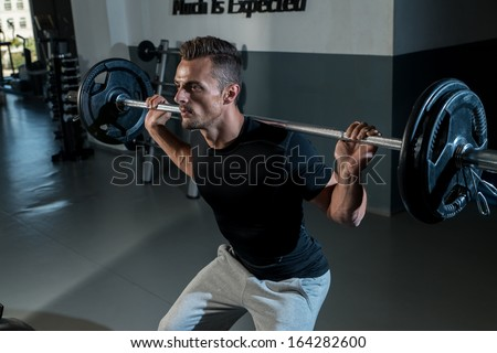 Man Doing Squats. Young Athlete Doing Barbell Squats