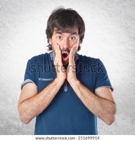 Man doing surprise gesture over textured background - stock photo