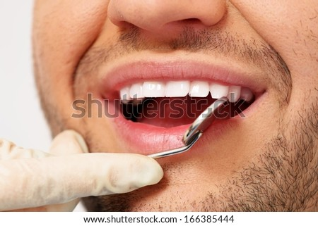 Man doing teeth checkup at dentist's surgery  - stock photo