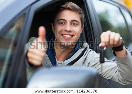 Man doing thumps-up in car - stock photo