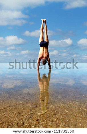 Man doing vertical handstand into the sea water - stock photo