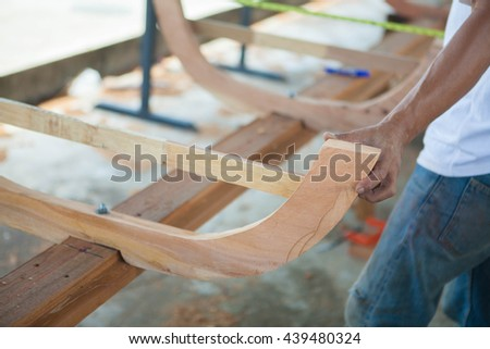 Man doing woodwork new boat in carpentry. Carpenter work on wood plank in workshop