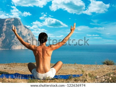 Man Doing Yoga at the Sea and Mountains - stock photo
