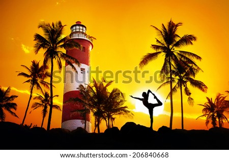 Man doing Yoga dancer pose in silhouette near lighthouse at sunset sky in Kovalam, Kerala, India - stock photo