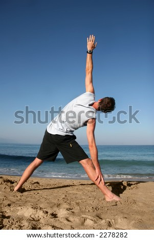 Man doing yoga exercise on the beach - stock photo