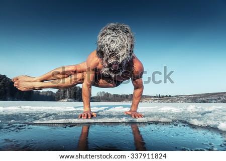 Man doing yoga exercise (parsva bakasana) on the ice of frozen lake - stock photo