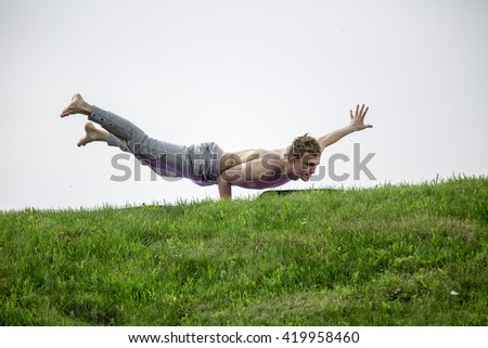 Man doing yoga exercises in the park. Fitness yoga man in cobra upward facing dog pose stretching abs stomach muscles. Fit male sports model doing stretching exercise outdoor in summer on grass. - stock photo