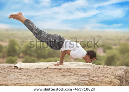 Man doing yoga in sunrise. Young man practicing yoga fitness exercise outdoor at beautiful mountains landscape. Morning sunrise. Meditation and relaxation