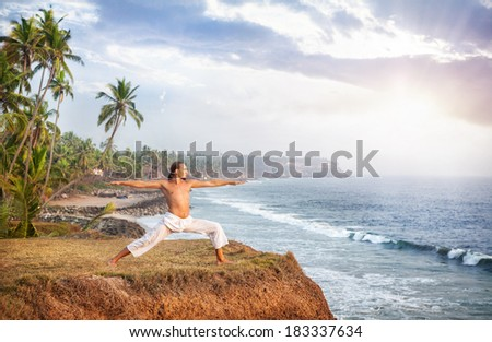 Man doing yoga in white trousers on the cliff near the ocean in Kerala, India - stock photo