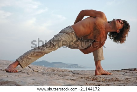 Man doing yoga outdoors. Parshvakonasana. Side view.