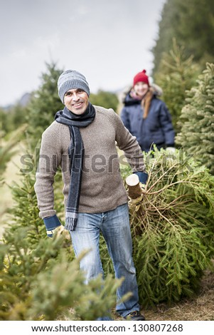 Man dragging fresh spruce at cut your own Christmas tree farm with his daughter in background - stock photo