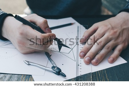 Man drawing a geometry sketch on the street caffee table - stock photo