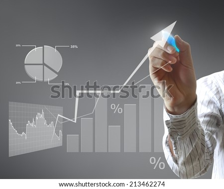 man drawing a graph on a glass wall  - stock photo