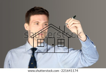Man drawing a house - focus on house - stock photo