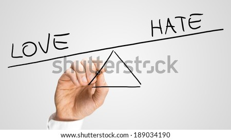 Man drawing a seesaw showing an imbalance between Love and Hate with the word positive being weighted more than the word negative on opposites ends. Concept of love conquering hate.