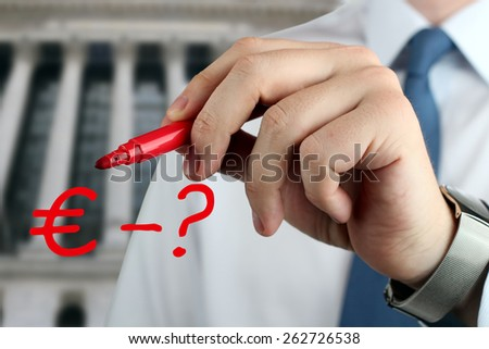 Man drawing a sign of  euro with question by red pen  - stock photo