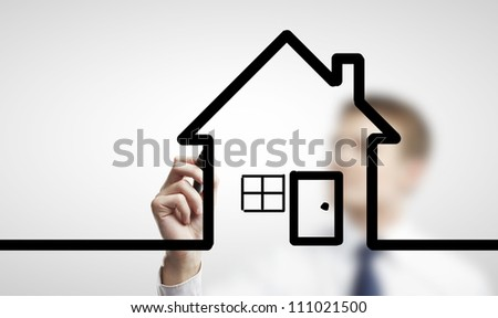 man drawing abstract house on a white background