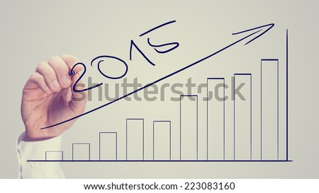 Man drawing an increasing bar graph dated for 2015 on a virtual interface as part of a business plan and strategy projecting increased growth and returns, vintage effect. - stock photo