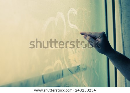 man drawing hearts in wet window - stock photo