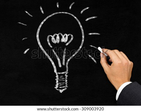Man drawing lightbulb with chalk on blackboard background - idea or innovation concept - stock photo