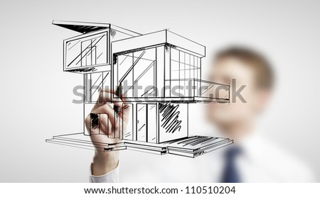 man drawing modern cottage on a white background - stock photo