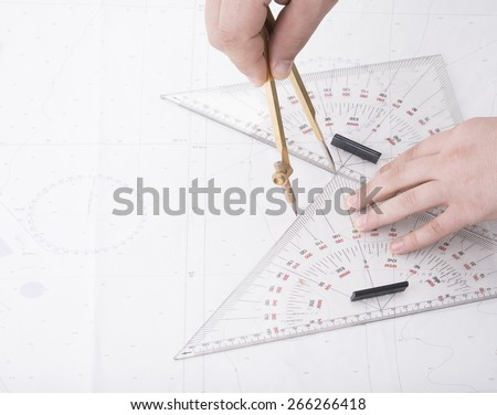 man drawing on ship map with divider and triangles - stock photo